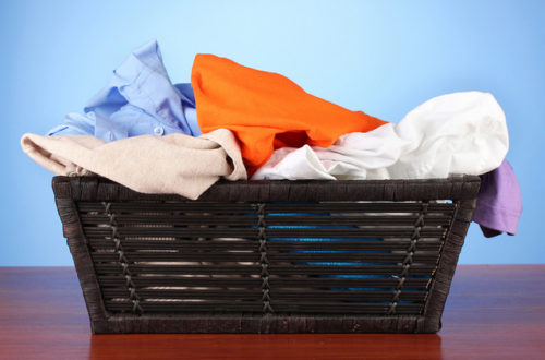 Bright clothes in laundry basket, on color background by Aqua Mechanical
